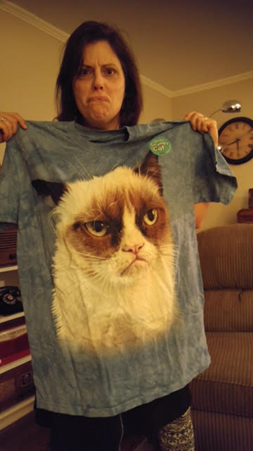 Me, making a grumpy face while holding my new Grumpy Cat t-shirt. The cat face is the size of an ottoman!