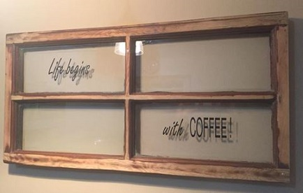 """wood-framed, four-pane window with """"Life begins"""" in script in the upper left pane and """"with coffee!"""" in the lower right pane. Coffee is in capital letters."""
