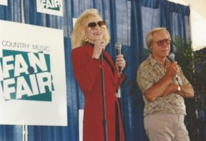 Very thin and frail-looking Tammy Wynette in a long, red blazer and sunglasses speaks on the mic next to George who looks like a typical old man who has money