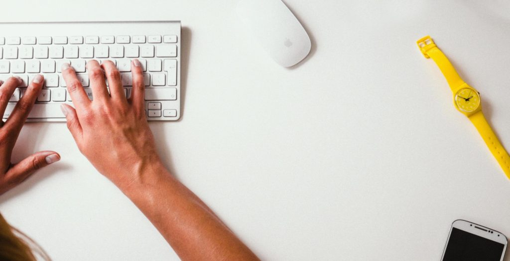 Hand on a laptop keyboard with a mouse and a yellow watch in view