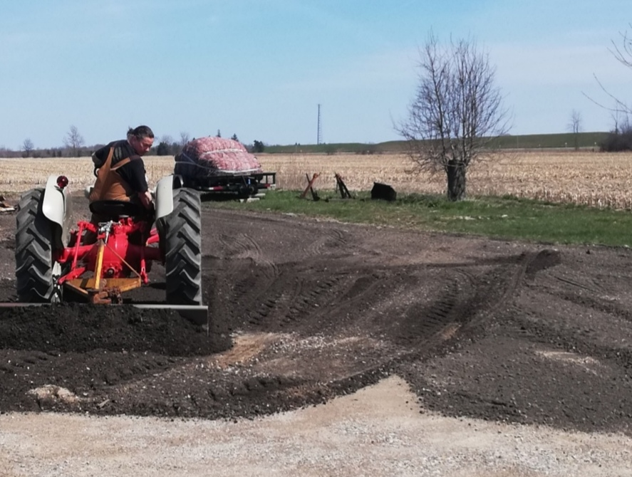 Derek on his red and grey tractor backing down from a pile of crushed asphalt, his blade pushing some of it