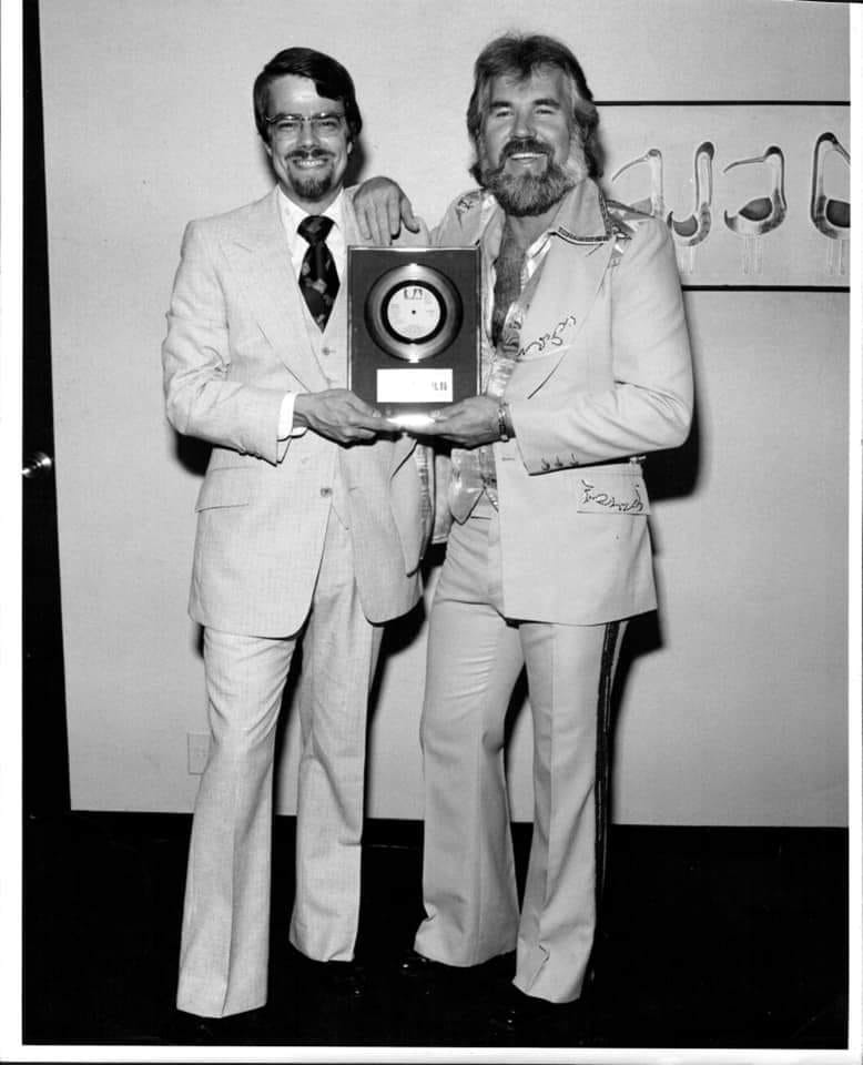 Nevin Grant and Kenny Rogers in a black and white photo, both wearing suits and holding a gold record