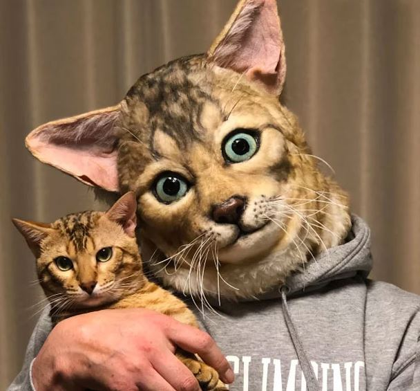 A man wears a cat mask or hood that looks just like the cat he's holding.