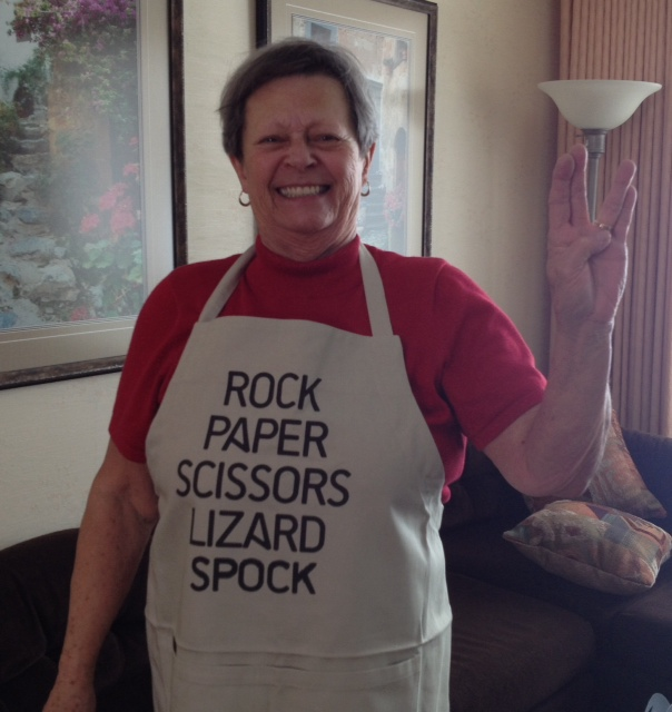 My Mom wearing a Big Bang Theory apron that reads Rock Paper Scissors Lizard Spock, and making the Live-long-and-prosper hand signal from Star Trek