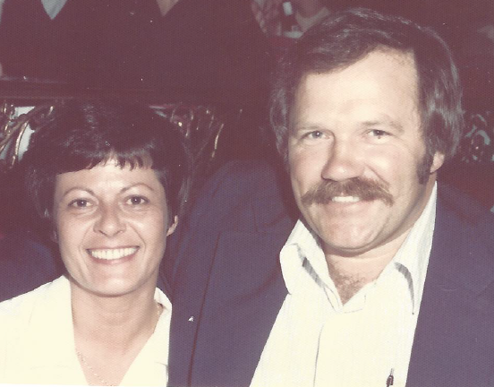 Mom and Dad smiling happily into the camera. Both around 40 years old. Mom is shorter, with short black hair. Dad is wearing a dinner jacket and has a moustache.