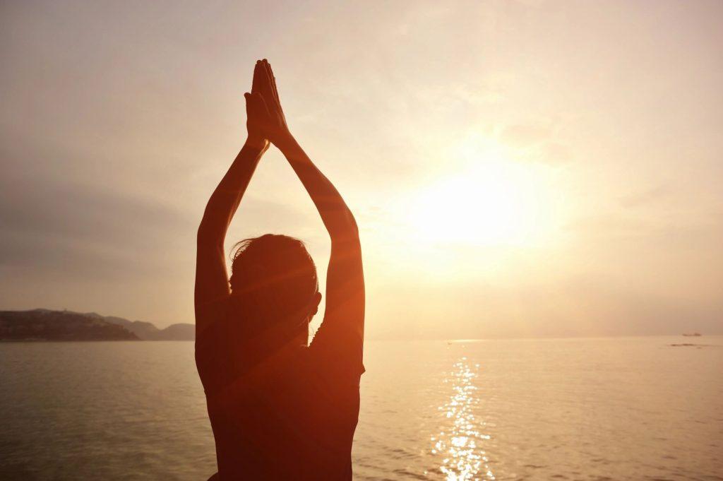 woman meditating as the sun rises