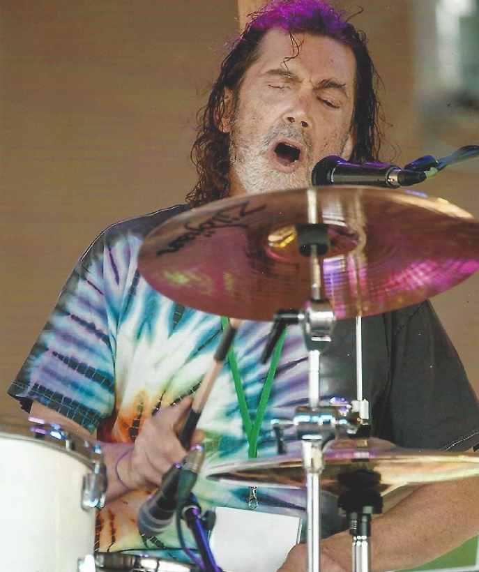 Brother Dave, eyes closed, drumming, with purple lights around him.