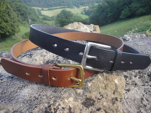 a brown and a black leather belt sitting on a rock