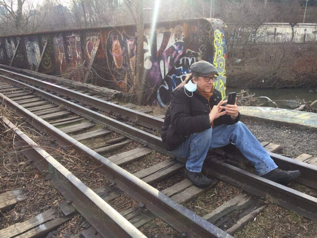 Our friend Louis with his mask hanging from one ear, sitting on train tracks looking at his phone with a wall of graffiti behind him.