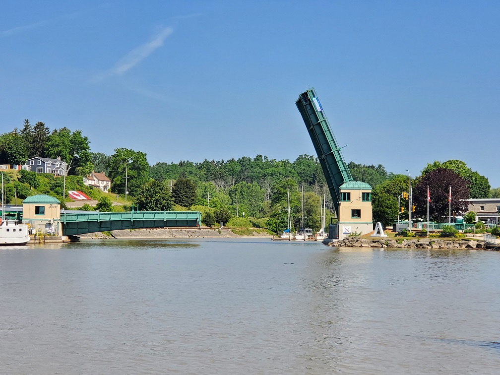 Long view of the lift bridge shows the left side down and the right side almost straight up. The sky is a perfect blue.