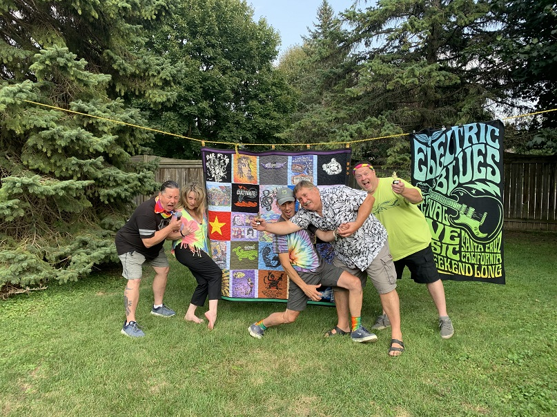 The five remaining Botten siblings all taking rock-star poses in front of a large quilt hanging on a clothes line. They're dressed in tie-dye colours and outside on grass with tall evergreens in the background.
