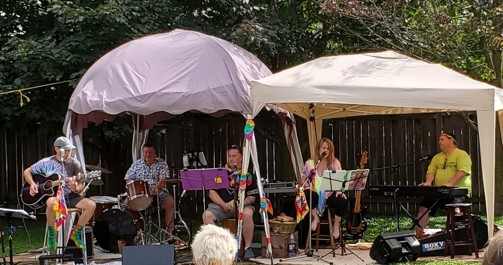 The five siblings, all dressed in bright colours and tie-die prints, performing under two canvas tents.