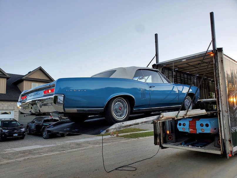 Bright blue Le Mans ragtop convertible suspended off the back of a tractor trailer on a metal tray.