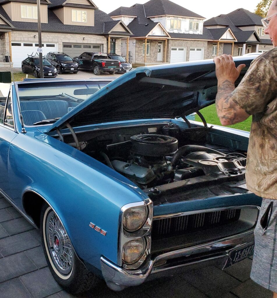 Derek opening the hood of the convertible, now in the driveway.