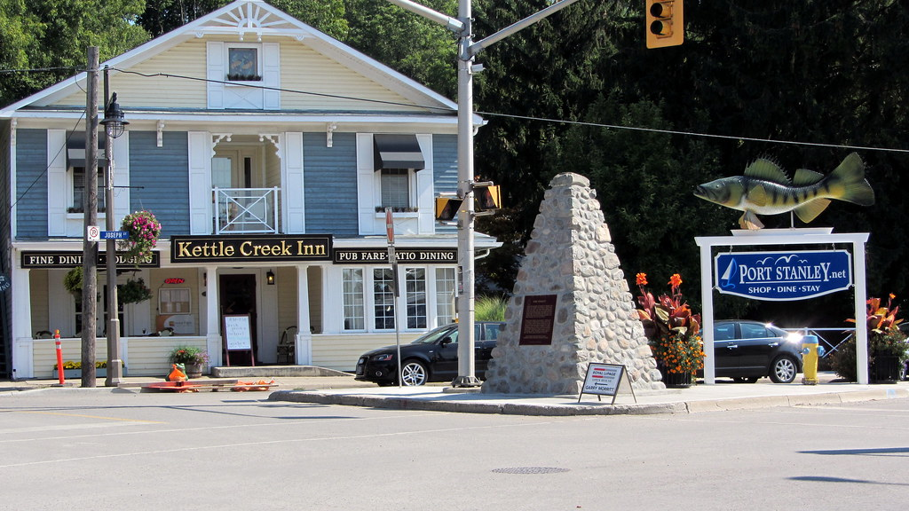 The Kettle Creek Inn, a large blue and white building, and the Port Stanley welcome sign that says shop, dine, stay. It has a big fish on top of it.